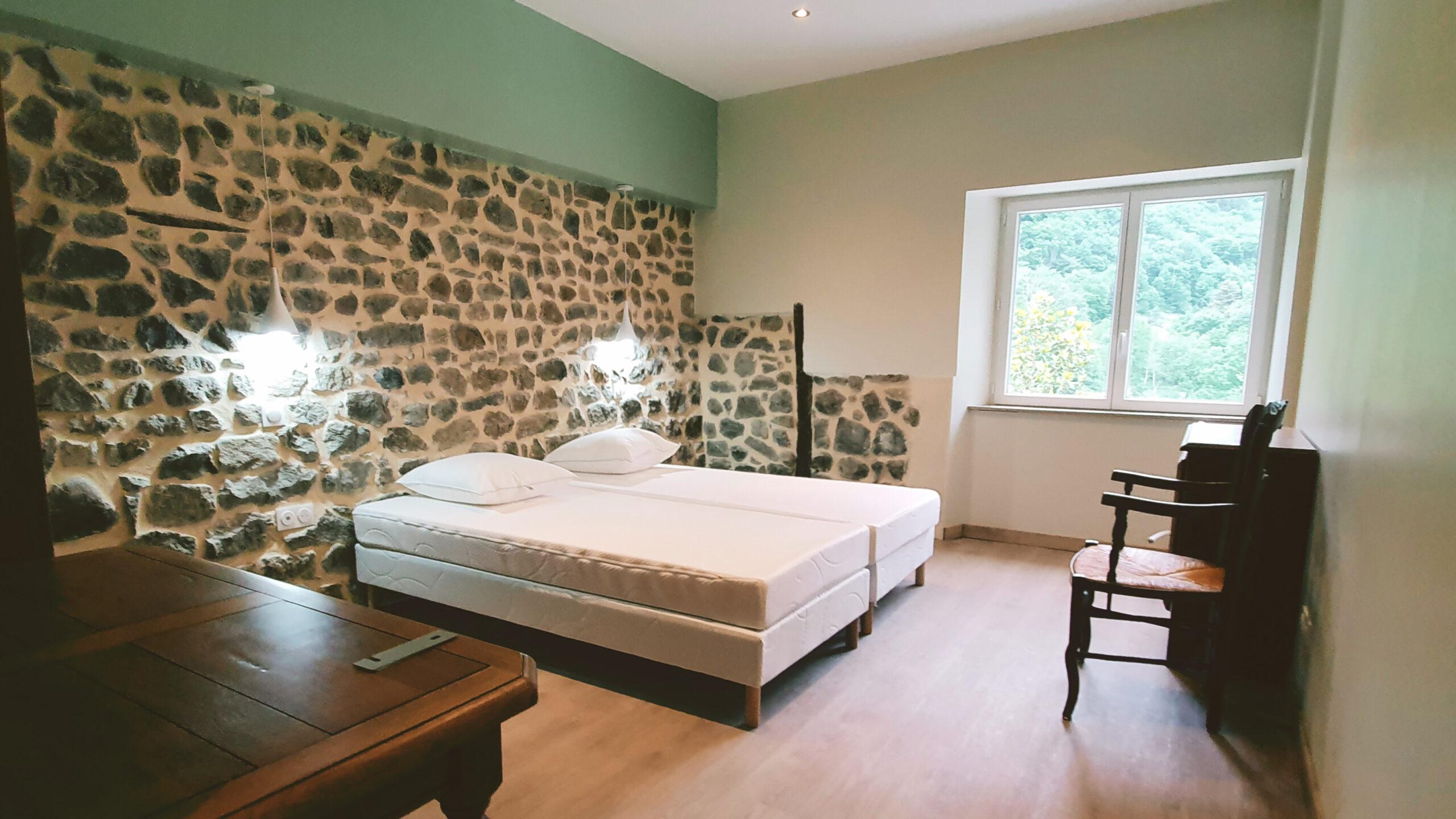 Chambre 4 avec mur de tete de lit en pierre décoration rustique