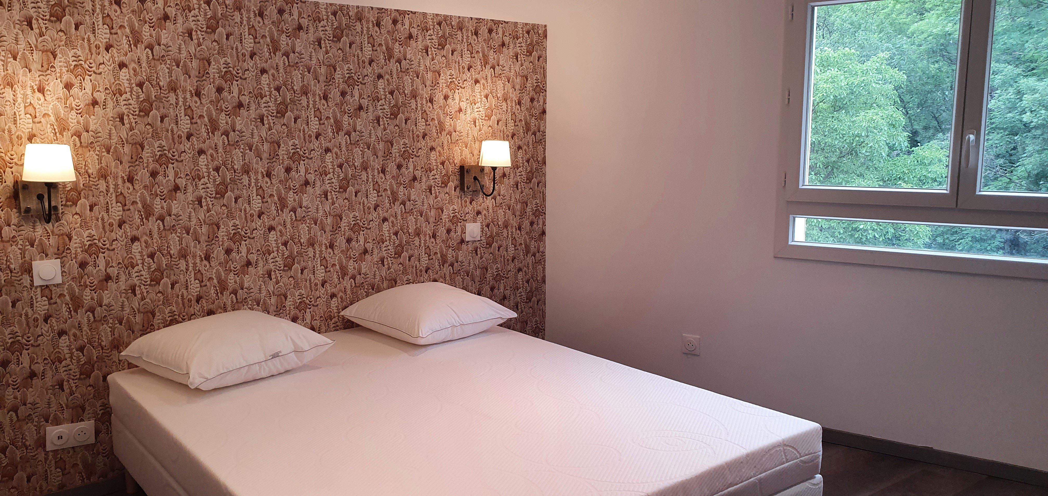 Chambre avec un mur tete de lit en papier peint et deux appliques