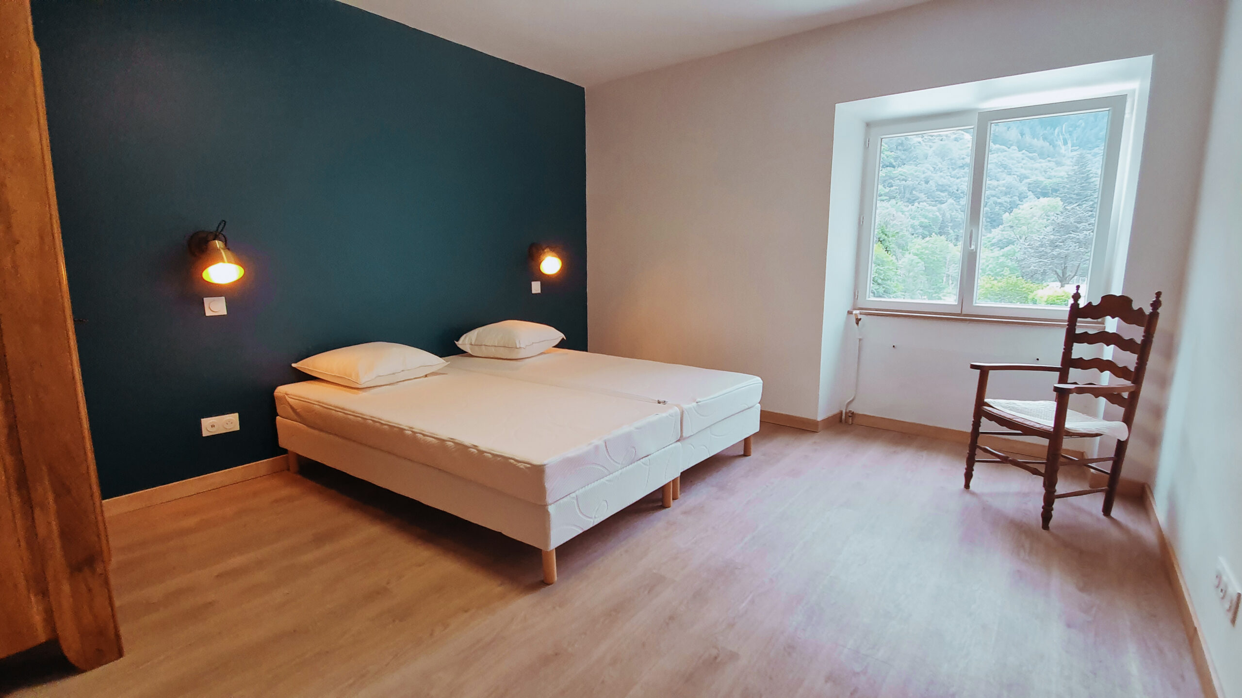 Chambre avec un mur bleu et une fenetre en ardeche